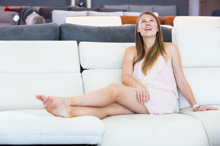 Portrait of positive woman buyer sitting barefoot on the sofa in furniture shop