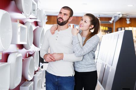 Young family couple choosing bathroom sink in bathroom fixtures store