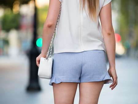 Close-up of female buttocks in blue short shorts on blurred cityscape background Stock Photo