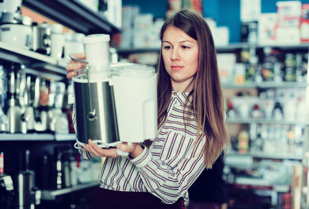 Young woman housewife looking  kitchen machine in household appliances shop