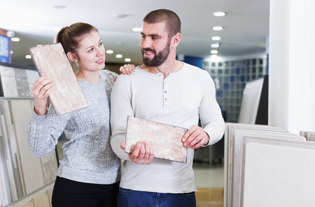 Young family customers standing with sample of ceramic tile  in  shop