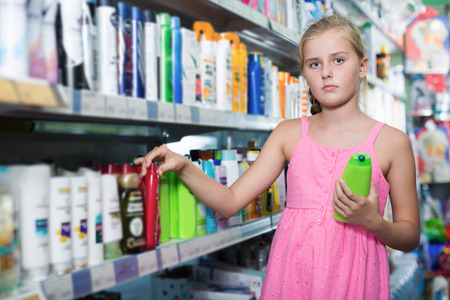 Young girl buying hair shampoo and conditioner at the shop Stock Photo