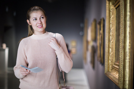 Portrait of young woman with guide looking at pictures at a museum of arts