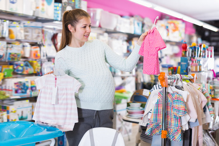 Modern girl is awating for baby and choosing clothes in the shop