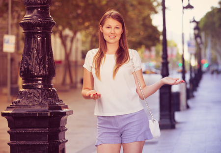 Smiling friendly girl inviting you to walk around summer city