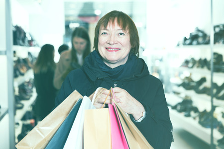 Adult woman is showing bags with purchases in shoes store.