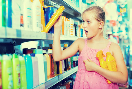 Astonished teenager girl choosing bottles of sun protection indoors in the shop Stock Photo