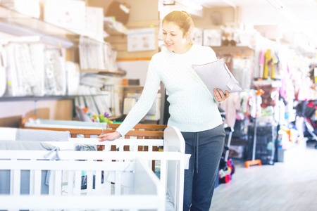 adult woman is awating for baby and choosing pillow for crib in the shop.