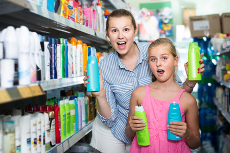 joyous woman with girl choosing shampoo and conditioner in the supermarket