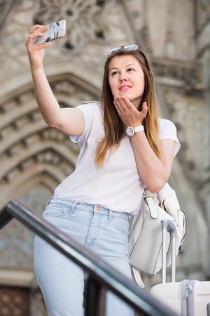 Attractive female tourist making selfie on the background of landmark Stock Photo