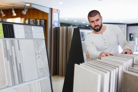 Portrait of man customer choosing ceramic tile  in domestic shop Stock Photo
