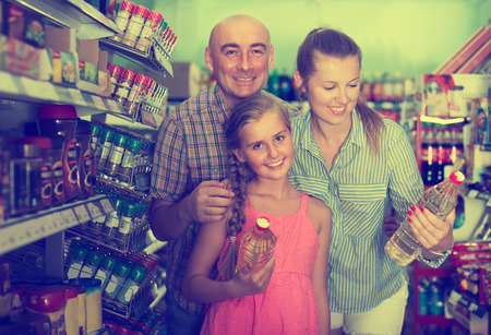 Mother with dad and daughter choosing sunflower oil at the supermarket