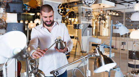 young smiling man  trying to use desk lamp in furniture showroom