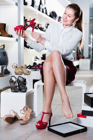 Young happy female is choosing summer shoes in shoes shop.