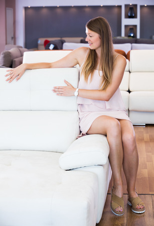 Glad woman   sitting and testing new sofa in the shopping room