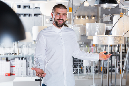 Male standing near lamp in the  designer furniture store indoor