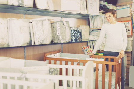Pregnant young female is buying crib for baby in the shop Stock Photo