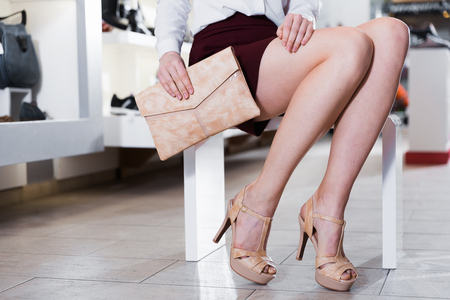 Close-up image of young woman who is posing with new handbag and fashion footwear in boutique.