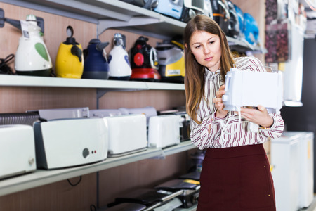 Positive girl looking for new modern toaster in store of kitchen appliances