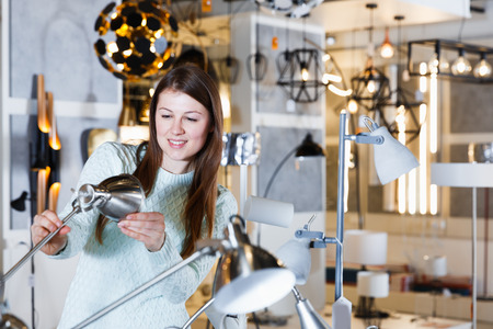 Portrait of young female  touching  desk lamp in furniture showroom
