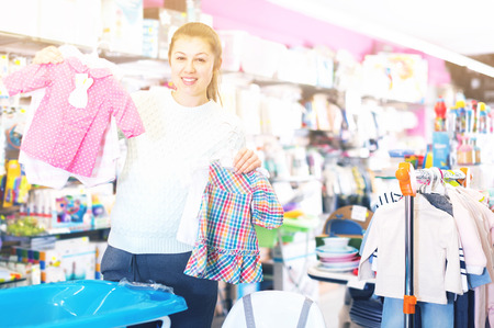 attentive pregnant female is buying clothes for baby in the childrens goods store Stock Photo