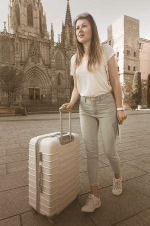 Attractive tourist blond woman taking walk in town with the travel bag Stock Photo