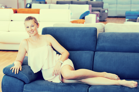 female customer barefoot relaxation and testing sofa in the furniture store