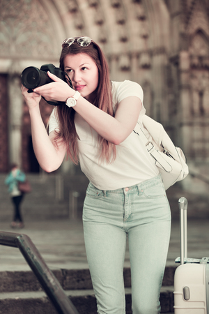Smiling young girl holding camera in hands and photographing in city