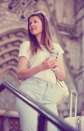 Young woman having mobile phone in hands and looking for the map in the phone Stock Photo
