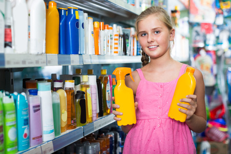 Young girl holding spray and lotion of sun protection at the shop