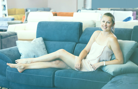 Young female customer barefoot choosing sofa in the furniture store with pillow