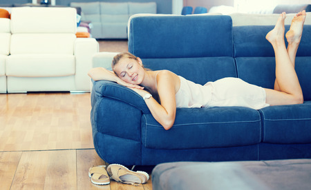 woman barefoot lying and relaxation on sofa in the shopping room Stock Photo
