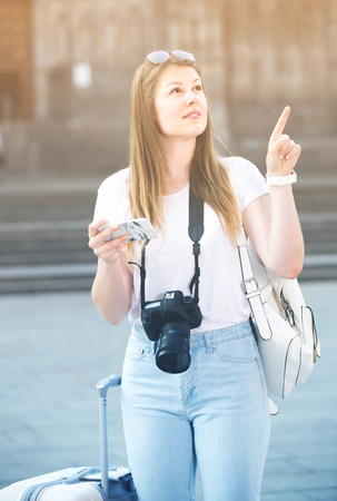 Smiling blonde girl is looking up the way in phone by using gps. Stock Photo