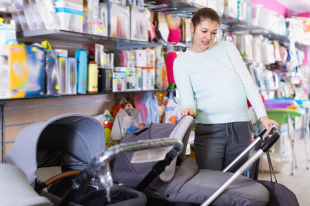 Happy cheerful  pregnant woman is choosing baby carriage in the shop.