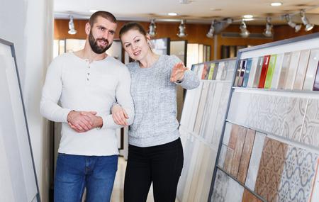 couple discusses kitchen ceramic tile  selection  in shop