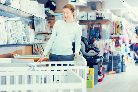 Pregnant female is selecting baby crib in the shop. Stock Photo