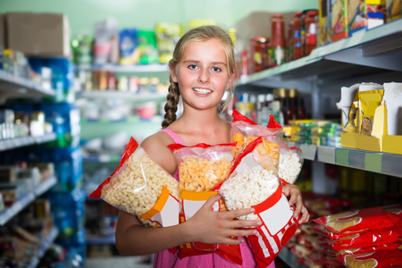 Customer girl is standing with packets of popcorn in the supermarket.