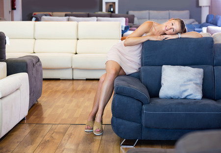 Adult glad  cheerful  female touching sofa in the furniture store before the buying Stock Photo