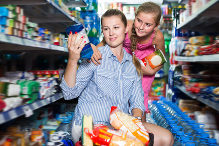 Adult mother with girl choosing rice with product basket Stock Photo