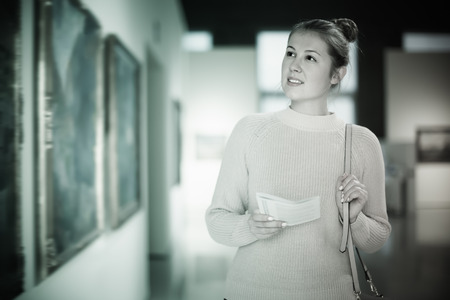 Portrait of beautiful woman looking at pictures and amaze in museum