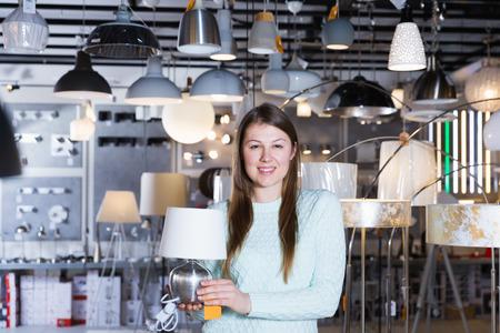 Smiling woman customer choosing torchere in furniture shopping room