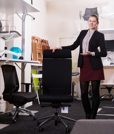 Confident woman seller of furniture shop proposing new model of ergonomic office chair Stock Photo