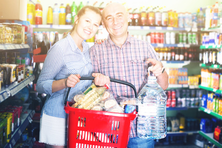 smiling woman and man with shopping basket with bottle of water in the supermarket