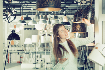 Positive girl buying plummed lamp in the modern furniture store Stock Photo