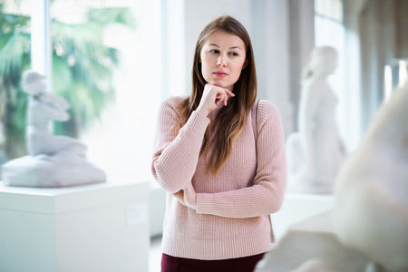 Portrait of young cheerful positive smiling woman standing near exposition  in art museum Stock Photo