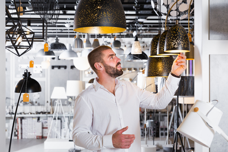 Young man choosing modern pendent lamp in  furniture  showroom Stock Photo