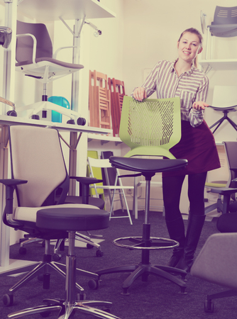 Confident woman seller of furniture shop suggesting new stylish model of bar stool Stock Photo