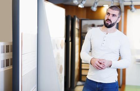 Smiling man customer choosing ceramic tile in domestic shop
