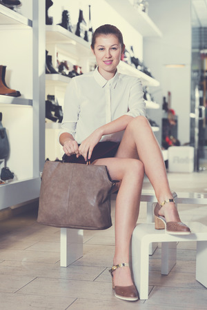 Portrait of smiling female customer who is posing with handbag in shoes store.
