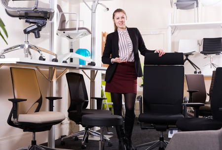 Young attractive saleswoman offering for sale comfortable office chair in furnishings store